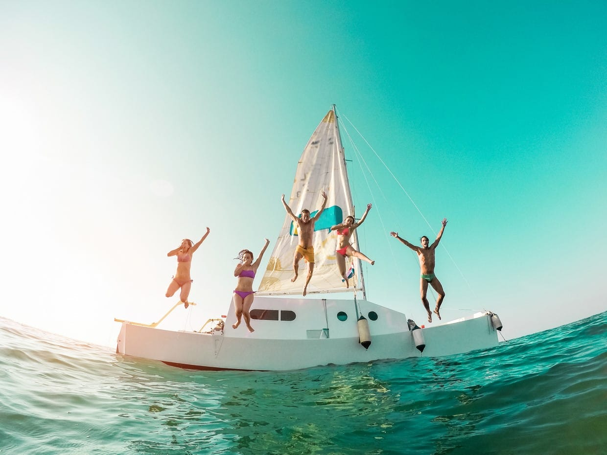 Happy crazy friends diving from sailing boat into the sea - Young people jumping inside ocean in summer vacation - Main focu