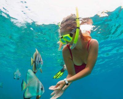 Girl in snorkeling mask dive in Bali